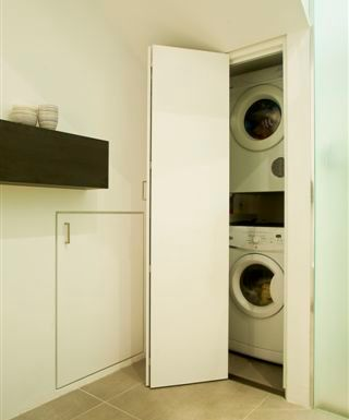 custom joinery hidden laundry in bathroom
